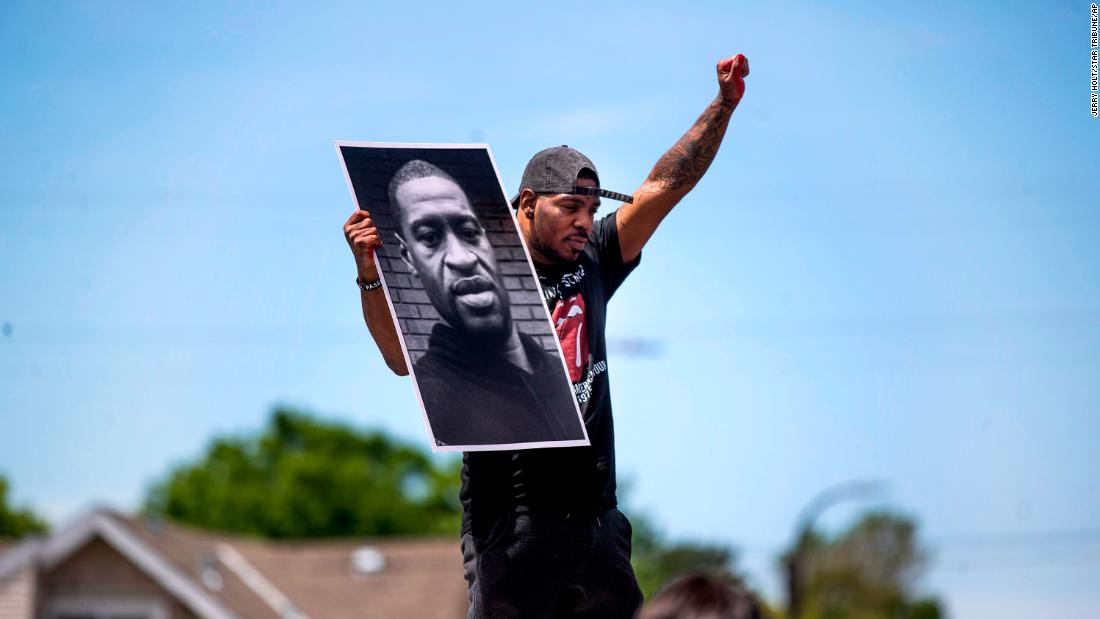 Tony L. Clark holds a photo of George Floyd outside the Cup Food convenience store, Thursday, May 28, 2020, in Minneapolis. Floyd, a handcuffed black man, died Monday in police custody near the convenience store. (Jerry Holt/Star Tribune via AP)